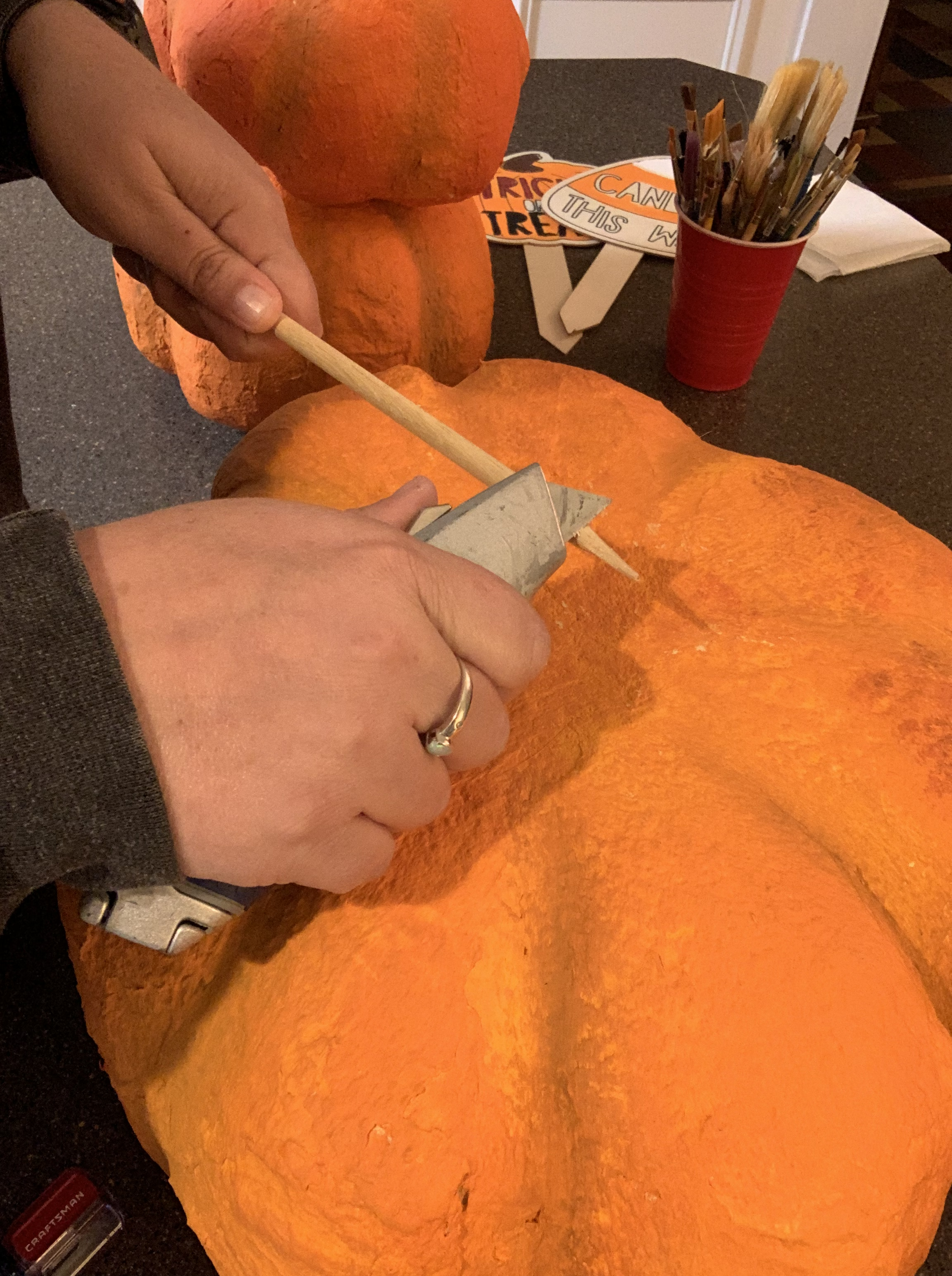 Sharpening a dowel rod to poke through the clay pumpkin forms