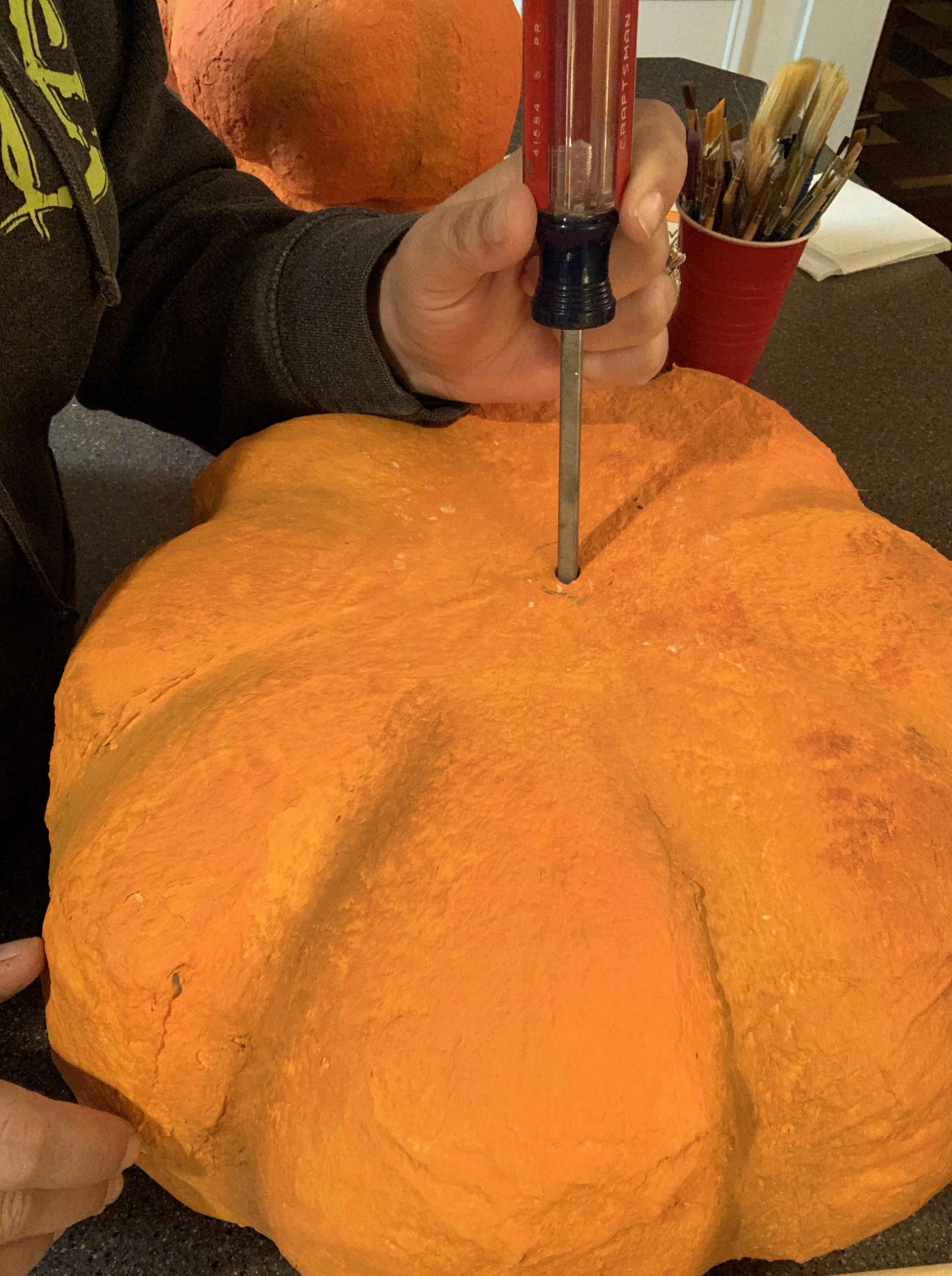 Using a screw driver to puncture holes in the clay pumpkins