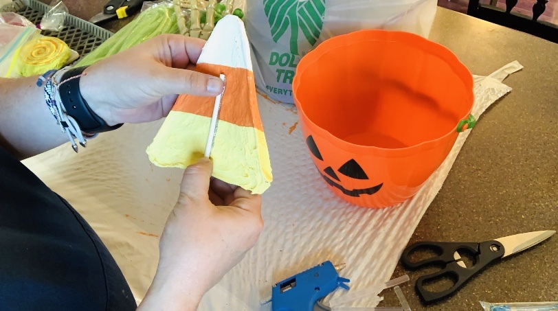 Hot gluing sticks on the candy paper maché to stick in the bucket