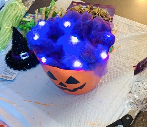 Faux spider webs fill the bucket and make the lights glow